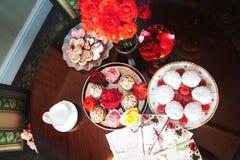 Os queques, o marshmallow e o doce de fruta encontram-se na tabela com uma xícara de café Foto de Stock