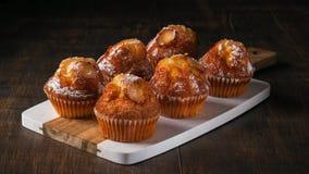 Os queques recentemente cozidos da baunilha com açúcar pulverizam, servido na placa de madeira horizontal imagens de stock