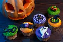 Os queques saborosos de Dia das Bruxas ajustaram-se com as decorações coloridas feitas de c foto de stock