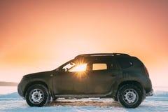 Os raios de sol através da janela do carro Renault Duster Or Dacia Duster Suv estacionaram no campo nevado do inverno no por do s imagem de stock