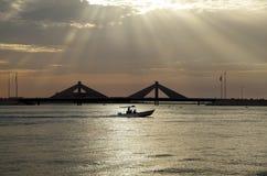 Os raios de sol e o barco de pressa perto de Sheikh Salman Causeway constroem uma ponte sobre Barém imagens de stock royalty free