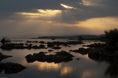 Os raios de sol quebram através das nuvens sobre silhuetas do tufo no mono lago durante o nascer do sol fotos de stock