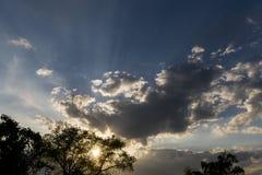Os raios de Sun brilham através do furo em nuvens pretas após a chuva Foto de Stock Royalty Free
