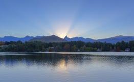 Os raios de Sun iluminam acima o céu atrás do pico de montanha Foto de Stock Royalty Free