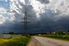 Os raios do ` s do sol brilham através das nuvens no fundo da linha de transmissão apoios imagens de stock