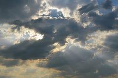 Os raios do sol brilham através das nuvens escuras Imagens de Stock