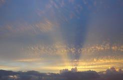 Os raios dourados do sol das nuvens de trás esticam através do céu acima imagem de stock