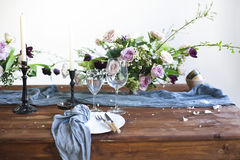 Os ramalhetes de flores cor-de-rosa em uma tabela ajustaram-se para o jantar com velas Imagens de Stock Royalty Free