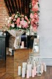 Os ramalhetes e as velas cor-de-rosa estão nas caixas de vidro antes do al do casamento imagens de stock
