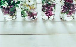 Os ramalhetes pitorescos da mola colorida florescem nas garrafas de vidro dos vasos, estando em seguido em uma tabela de madeira  Imagem de Stock