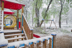 Os ramos da árvore com as folhas verdes da mola quebraram sob o peso da neve e do vento molhados, na área do sono Imagens de Stock