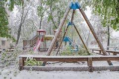 Os ramos da árvore com as folhas verdes da mola quebraram sob o peso da neve e do vento molhados, na área do sono Foto de Stock Royalty Free