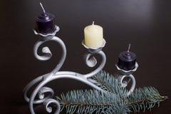 Os ramos da mentira spruce azul no plano Entre eles, as velas são brancas e pretas em um castiçal forjado Imagem de Stock Royalty Free