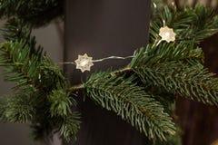 Os ramos de árvore verdes do Natal decorados com festão macia iluminam-se Fotografia de Stock
