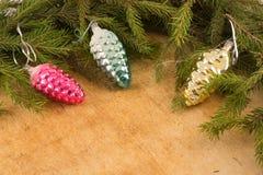 Os ramos de árvores de Natal e de decorações fallal do cone no fundo de placas de madeira Fotografia de Stock Royalty Free