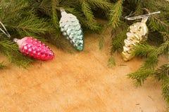 Os ramos de árvores de Natal e de decorações fallal do cone no fundo de placas de madeira Fotos de Stock Royalty Free