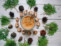 os ramos do cipreste, de uma xícara de café, de cones da floresta e de nozes encontram-se em um fundo branco imagens de stock