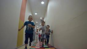 Os rapazes pequenos alegres raça e têm o divertimento brilhantemente no corredor do Lit vídeos de arquivo