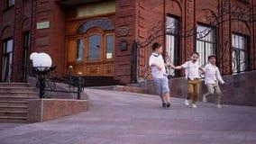 Os rapazes pequenos em um retro à roupa jogam um jogo da etiqueta na rua video estoque