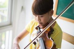 Os rapazes pequenos jogam e praticam o violino na classe de música imagens de stock