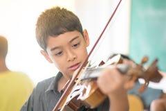 Os rapazes pequenos jogam e praticam o violino na classe de música foto de stock royalty free