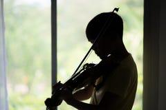 Os rapazes pequenos jogam e praticam o violino na classe de música foto de stock