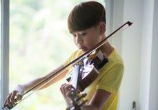 Os rapazes pequenos jogam e praticam o violino na sala de classe da música imagem de stock