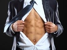 Os rasgos do homem de negócio abrem sua camisa em uma forma do super-herói que obtem pronta para salvar o dia imagem de stock