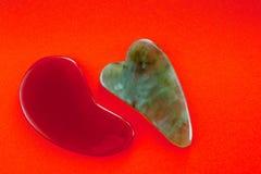 Os raspadores de Guasha para a massagem do corpo de acordo com o método antigo dispararam em um fundo vermelho brilhante imagem de stock