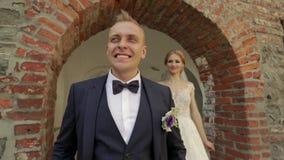 Os recém-casados estão andando no castelo em seu dia do casamento Os noivos Enjoying no dia do casamento video estoque