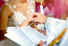 Os recém-casados estão antes do padre em uma cerimônia de casamento e trocam os anéis imagens de stock