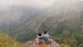 Os recém-casados felizes do tiro largo traseiro da vista sentam junto o aperto sob a chuva no curso da lua de mel em montanhas ép filme
