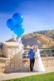 Os recém-casados felizes guardam balões grandes azuis ao levantar antes do autu imagens de stock
