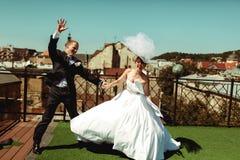 Os recém-casados felizes têm a dança do divertimento no telhado Imagens de Stock