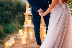 Os recém-casados guardam as mãos na cerimônia de casamento Terra arrendada dos pares imagem de stock royalty free