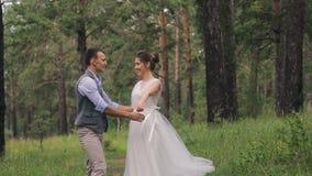 Os recém-casados na sessão fotográfica na floresta que anda, apreciam momentos fora filme