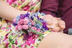 Os recém-casados novos estão guardando as mãos com um ramalhete que se encontre no regaço do ` s da noiva fotografia de stock royalty free