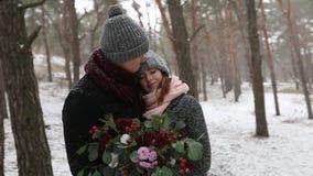 Os recém-casados preparam e o beijo do abraço da noiva e aquecem-se na floresta nevado do pinho durante a queda de neve no movime video estoque