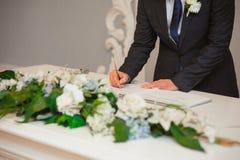 Os recém-casados puseram suas assinaturas em pleno ato de registrar uma união imagens de stock royalty free