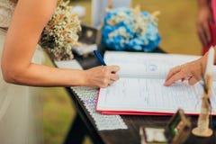 Os recém-casados puseram suas assinaturas em pleno ato de registrar uma união imagens de stock