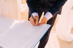Os recém-casados puseram suas assinaturas em pleno ato de registrar uma união fotos de stock