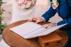 Os recém-casados puseram suas assinaturas em pleno ato de registrar uma união fotografia de stock royalty free