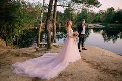 Os recém-casados que estão no lago suportam no por do sol Fotografia de Stock Royalty Free