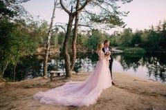 Os recém-casados que estão no lago suportam no por do sol Imagem de Stock Royalty Free