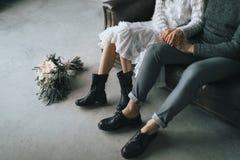 Os recém-casados sentam-se em casa no sofá Pés em botas ocasionais de pares novos Imagem de Stock