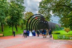 Os recém-casados tomam fotos pela entrada à ponte de Andreevsky no Mo Foto de Stock Royalty Free