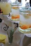 Os recipientes de vidro do fruto infundiram a água na tabela de bufete Imagem de Stock Royalty Free