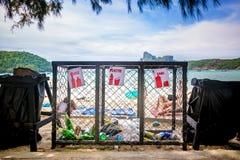 Os recipientes do lixo para separado desperdiçam a coleção na praia tropical perto dos povos que banho de sol foto de stock royalty free