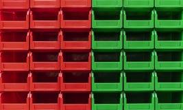 Os recipientes verdes e vermelhos plásticos são empilhados em diversas fileiras fotos de stock