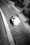 Os recém-casados que andam abaixo da pedra pisam bw Foto de Stock